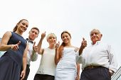 Successful business team holding thumbs up and smiling