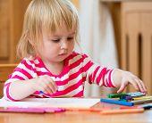Cute three-year-old girl draws felt-tip pens at home