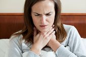 stock photo of pharyngitis  - Woman having a sore throat lying in bed - JPG