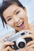 Happy smiling Chinese Asian young woman or girl in a bikini at the beach taking a photograph using a retro digital camera