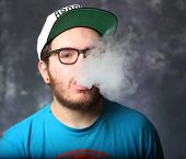 foto of exhale  - Young man in Brooklyn baseball exhaling vapor from electric cigarette against portrait background - JPG