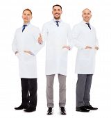 healthcare, profession and medicine concept - smiling male doctors in white coats over white background