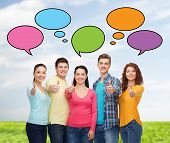 friendship, communication, gesture and people concept - group of smiling teenagers showing thumbs up over sky and grass with text bubbles