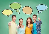 school, education, communication, gesture and people concept - group of smiling teenagers showing thumbs up over green board background with text bubbles