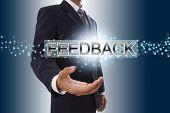 Businessman hand showing feedback button.