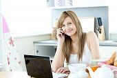 Caucasian Woman Using A Laptop And A Phone In The Kitchen