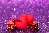 Decorative handmade hearts and gifts on shiny glitter background