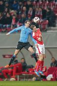 KLAGENFURT, AUSTRIA - MARCH 05, 2014: Diego Godin (#3 Uruguay) and Marc Janko (#21 Austria) fight for the ball in a friendly soccer game between Austria and Uruguay.