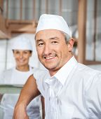 Portrait of confident male mature butcher smiling with female colleague in background at butchery