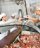Mature male customer paying through smartphone at butchery