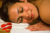 Happy brunette lying in a sauna against heart