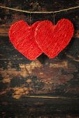 Red  hearts  hanging on the clothesline. On old wood background