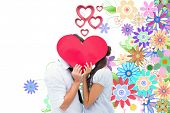 stock photo of girly  - Couple covering their kiss with a heart against digitally generated girly floral design - JPG