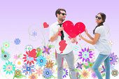 Hipster couple smiling at camera holding a heart against digitally generated girly floral design