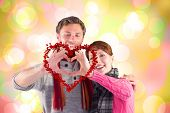 pic of girly  - Couple making a heart shape against girly pink and yellow pattern - JPG