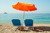 Blue Sunbeds And Orange Umbrella (parasol) On Paradise Beach In Corfu Island, Greece.