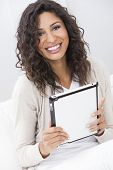 Beautiful young Latina Hispanic woman smiling, relaxing and using a tablet computer