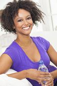 Beautiful young mixed race black African American woman smiling, relaxing and drinking a bottle of water at home on a sofa