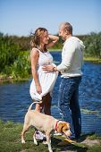stock photo of caress  - A husband is caressing his pregnant wife at a outdoor lake - JPG