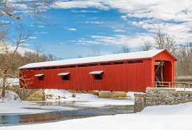 stock photo of cataracts  - The red Cataract Falls Covered Bridge in rural Indiana crosses Mill Creek in a snowy winter landscape with a cloudy blue sky - JPG