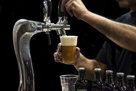 image of tapping  - Man drawing beer from tap in an plastic cup - JPG