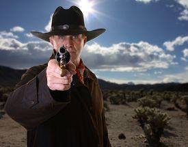 stock photo of gunfights  - Cowboy pointing gun with selective focus on gun against desert background  - JPG