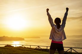 image of athletic woman  - Successful sporty woman raising arms towards golden beautiful sunset and sea - JPG