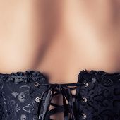 foto of corset  - woman wearing black corset and pearls against retro background - JPG