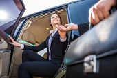 stock photo of laws-of-attraction  - Young beautiful smiling businesswoman in suit coming out of her luxurious car - JPG