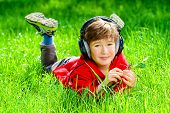 picture of 7-year-old  - 7 years old boy lying on a grass and listening to music in headphones - JPG