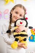 stock photo of pullovers  - Little pretty smiling girl in white pullover with toy bee on colorful background - JPG