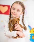 picture of pullovers  - Little pretty smiling girl in white pullover with teddy on colorful background - JPG
