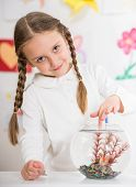 picture of pullovers  - Little pretty smiling girl in white pullover playing with gold fish in aquarium on colorful background - JPG