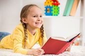 stock photo of pullovers  - Little pretty girl in yellow pullover reading book on colorful background - JPG