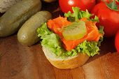 picture of baguette  - Slice of baguette with pollock fillet garnished with lettuce onion tomato and pickles on a wooden board - JPG