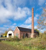 stock photo of dutch oven  - exterior of an old decayed building with brick chimney - JPG