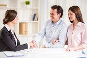 foto of contract  - Young couple signing financial contract with female realtor - JPG