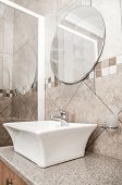 stock photo of granite  - A modern bathroom basin placed on a granite topped cupboard inside the bathroom - JPG