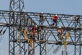 stock photo of power transmission lines  - workers on electricity poles - JPG
