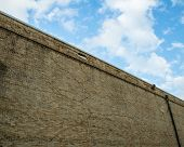 picture of wall cloud  - Brick wall with clouds in the background and multiple crack patterns showing - JPG