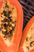 stock photo of pawpaw  - Two slices of ripe papaya with pyrenes on wicker background - JPG