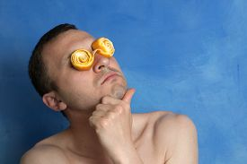 stock photo of wacky  - Portrait of a Thinking Man With Crazy Orange Peel Spectacles on Blue Background - JPG