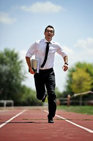 image of running-late  - businessman in shirt and necktie carrying folder portfolio and files running in stress on athletic track looking stressed and late for the meeting in work urgent problems metaphor - JPG