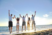 stock photo of summer beach  - happy young friends group have fun and celebrate while jumping and running on the beach at the sunset - JPG