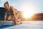 Female Sprinter In Track Starting Blocks poster