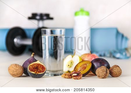 poster of Healthy lifestyle concept. Diet and fitness. Healthy lifestyle style. Water and fruit as a healthy food on a background of blurry fitness equipment. Proper nutrition and active healthy lifestyle.