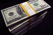 image of ten thousand dollars  - Stack of Ten Thousand Dollar Piles of One Hundred Dollar Bills on a black background - JPG