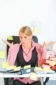 Shocked by set of tasks modern business woman sitting at workplace covered with sticky notes