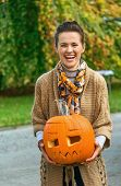 Woman On Halloween Outdoors Showing Carved Pumpkin poster