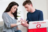Young man bandage his girlfriend with first aid kit at home after an injury